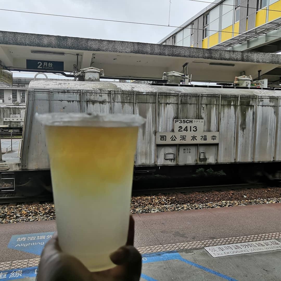 火車站月台前,拿著一杯飲料